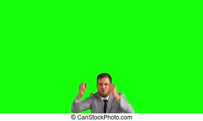 Businessman jumping and cheering on green screen in slow...