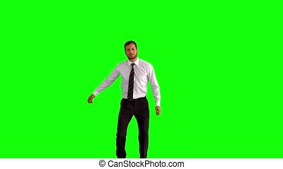 Businessman jumping up and clicking his heels on green...