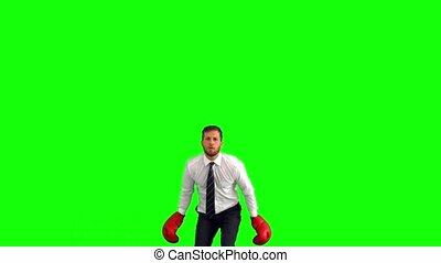 Businessman leaping with boxing gloves and hitting fists...