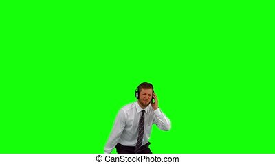 Businessman listening to music while jumping up on green...