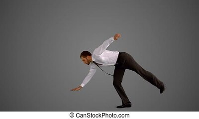 Businessman doing one hand handstand on grey background in...