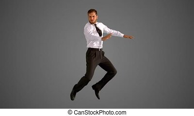 Businessman jumping on grey background in slow motion