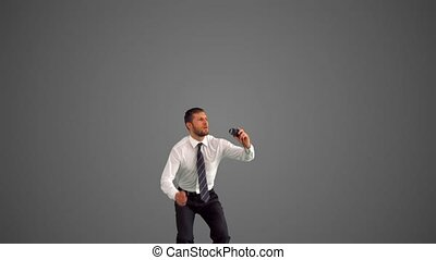 Businessman jumping and punching air on grey background in...