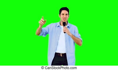 Man singing into microphone and dancing on green screen in...