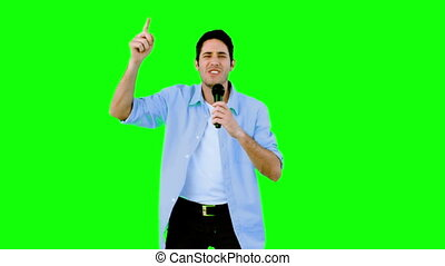 Man singing into microphone on green screen in slow motion