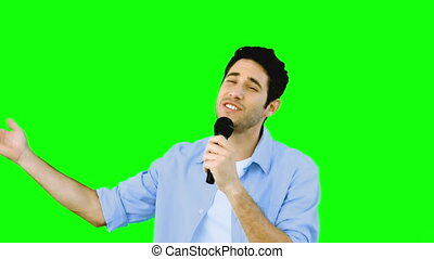 Man singing into microphone with emotion on green screen in...