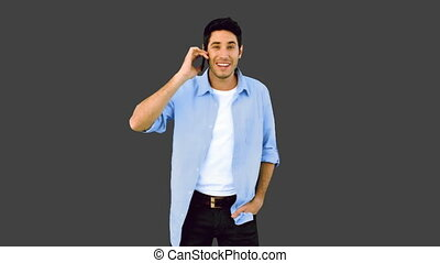 Man talking on phone and laughing on grey background in slow...