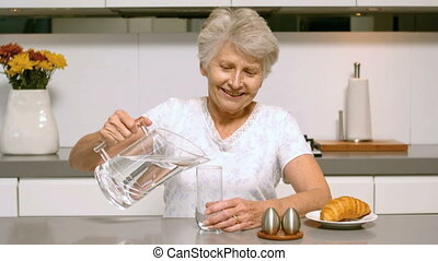 Retired woman pouring glass of water for breakfast in the...
