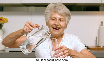 Retired woman pouring glass of water in the kitchen in slow...