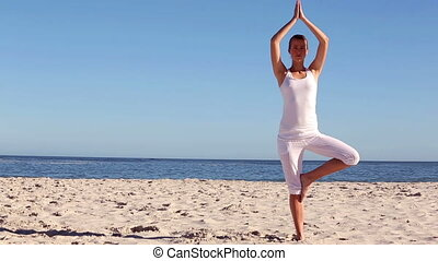 Woman practicing yoga on the beach - Woman practicing yoga...