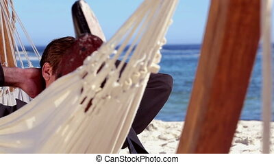 Businessman relaxing in a hammock on a sunny beach