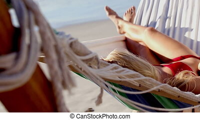 Attractive woman in red bikini in a hammock on a sunny beach