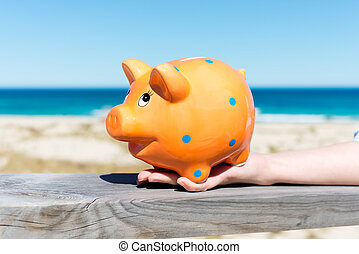 piggy bank standing by the beach - woman´s hand holding...