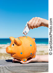 Womans Hand Inserting Euro Note In Piggybank At Beach -...