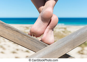 Womans Bare Feet On Wood At Beach - Closeup of womans bare...