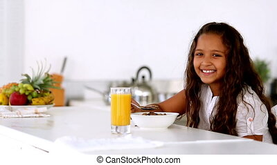 Little girl smiling at camera at breakfast in kitchen