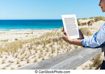Woman Reading E-Reader At Fence On Beach - Mid adult woman...