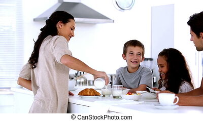 Mother chatting to children at family breakfast and pouring...