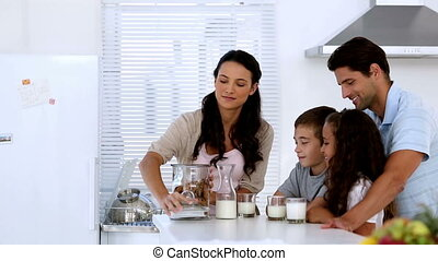 Mother giving cookies to her family with milk in the kitchen