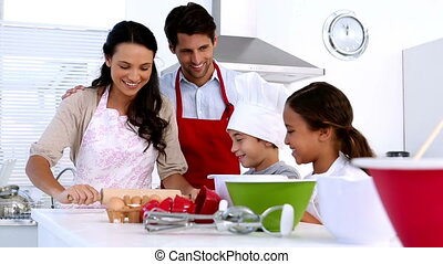 Family preparing cake together at home in kitchen