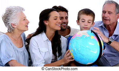 Extended family looking at globe together at home on sofa