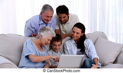 Extended family using laptop together at home on the couch