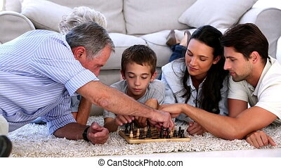 Extended family playing chess at home on the living room...
