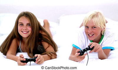 Siblings playing video games together at home on bed
