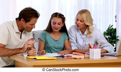 Parents proud of their daughters homework at desk in living...