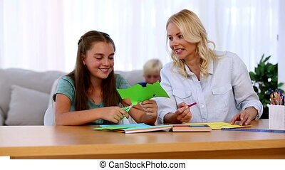 Mother and daughter doing arts and crafts at home in living...