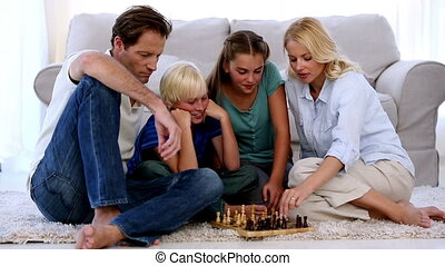 Children and parents playing chess at home on living room...