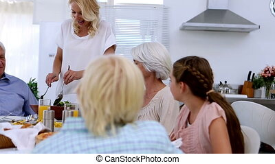 Woman serving salad at dinner table to her extended family