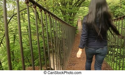 Rope Bridge Woman Walking - rope bridge in a forest
