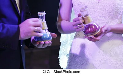 Sand ceremony - Bride and groom are mixed multicolored sand...