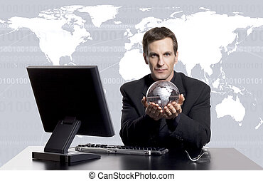 Travel agent - Businessman at his desk holding a globe with...