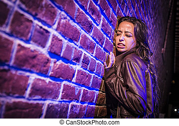 Frightened Pretty Young Woman Against Brick Wall at Night -...