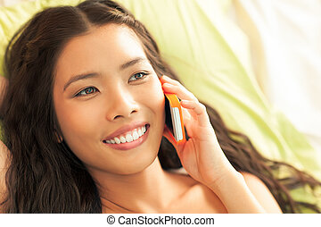Woman Telephoning - Smiling Asian woman making a phone call.