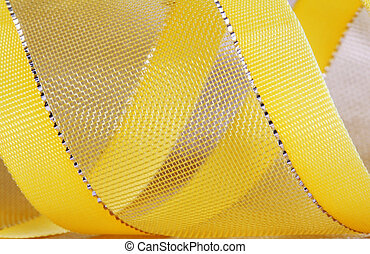yellow ribbon - Macro shot of a yellow ribbon with golden...