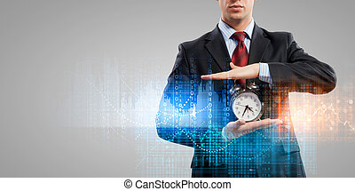 Business man holding alarmclock - Image of businessman...