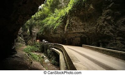 Street SP38 at lake garda in Italy - cars in a canyon on the...