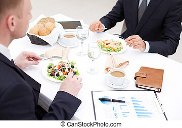 Business lunch - Close-up of businessmen sitting in cafe and...