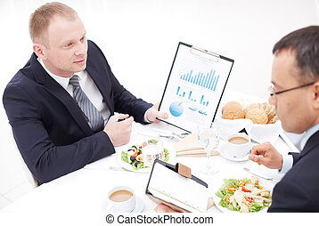 Eating meeting - Two businessmen discussing paper and...