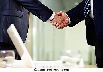 Symbol of cooperation - Close-up of two men handshaking...