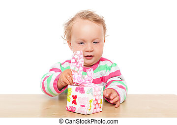 Baby girl unwrapping present - Cute one year old blonde baby...