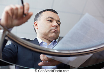Businessman reading document - Close-up of pensive...