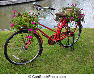 Red painted bicycle with a bucket of colorful flowers.