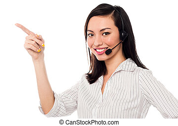 Asian call center executive pointing away - Cheerful female...