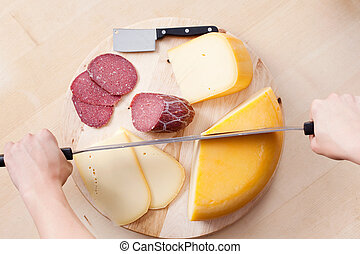 Cutting cheese and sausage - Worker cutting cheese and...