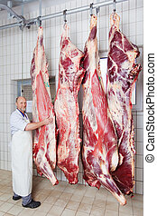 Butcher posing with peeled bodies of cow in his shop