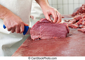 Butcher's hand - Worker cutting the meat on a wooden board